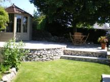 Copyright image: Garden design - a beautiful summerhouse kit on a raised patio area.