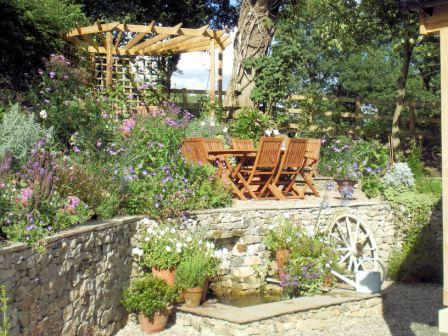 Copyright image: A wonderful corner pergola design in a romantic cottage garden.