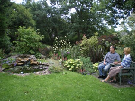Copyright image: Natural pond with love seat and plants as part of a garden makeover.