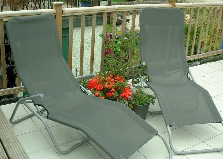 Copyright image: Sun loungers with potted plants on a roof garden.