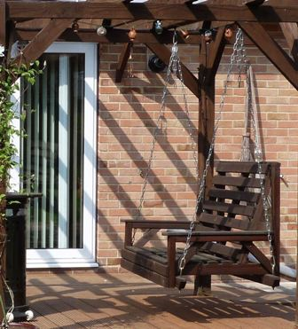 Copyright image: Hanging seat as part of an attached lean-to pergola design.