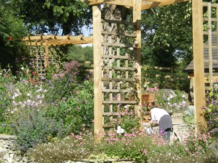 Copyright image: A pergola arch and stunning corner pergola in a wonderful cottage garden.