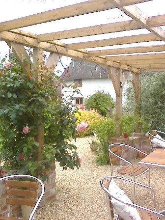 Copyright image: A fantastic attached lean-to pergola with lovely climbing roses growing up the pergola posts.