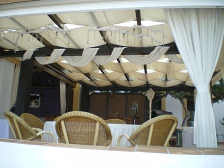 Copyright image: An beautiful attached lean-to pergola used for outdoor dining, overlooking the sea.
