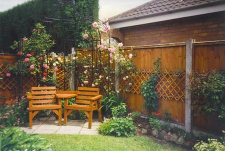Copyright image: A metal gazebo with love seat  and climbing plants.