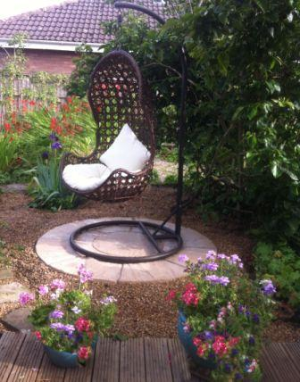 Copyright image: An interesting garden feature with a hanging chair and patio circle.