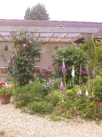 Copyright image: A fantastic attached lean-to pergola with lovely cottage garden planting.