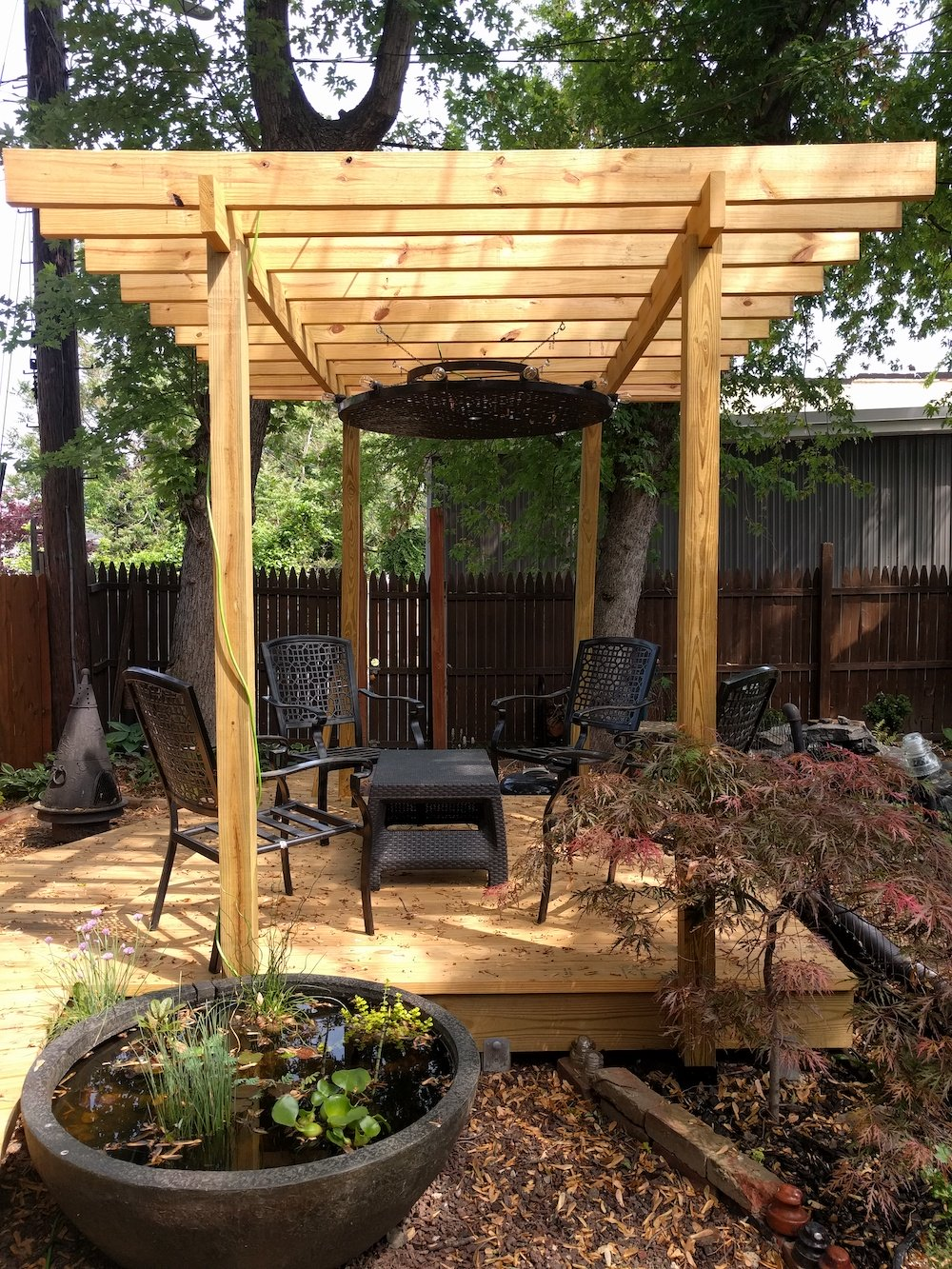 Copyright image: modern pergola with central hanging light feature.